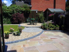 AFTER INDIAN STONE PATIO WITH CURVED THEMED GARDEN GRASSENDALE